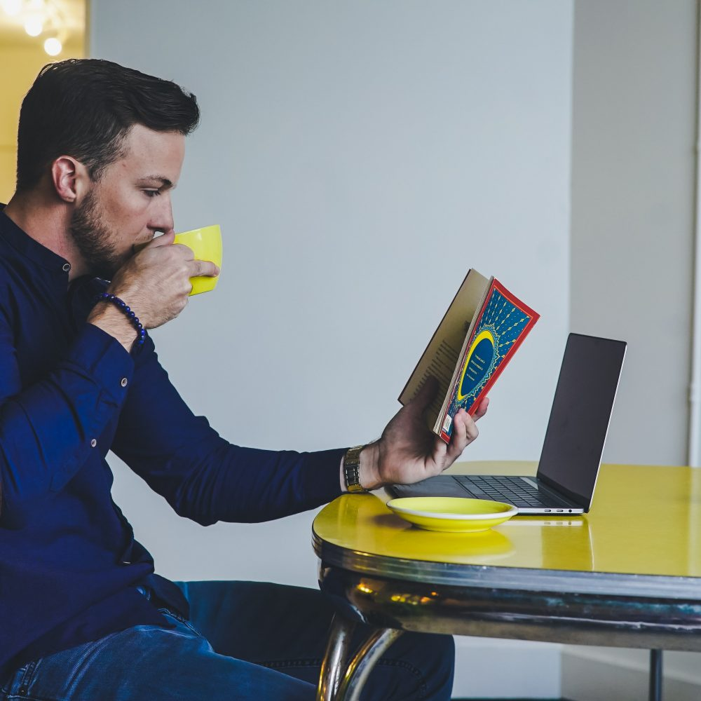 man reading books at laptop